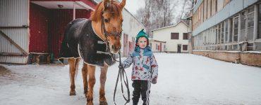 Cheval avec une couverture tenu par un enfant