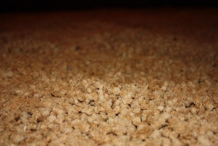 Mise en place de granulés de bois dans un box